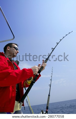 Fisherman fishing on boat big game tuna, blue sunny sky - stock photo