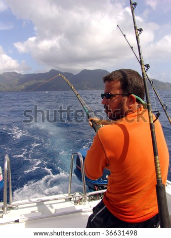 Fisherman fishing on boat in ocean on Seychelles - stock photo