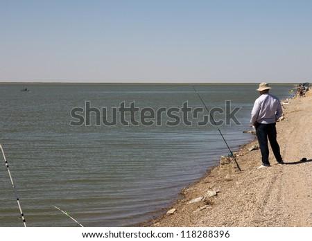 Fisherman fishing on the lake - stock photo