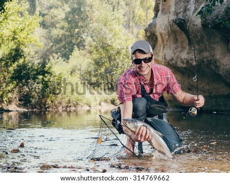 Fisherman. Fishing on the river fly fishing. Man fisherman holds in hand large catch fish. - stock photo