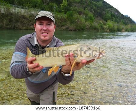 fisherman holding a fresh caught fish  - stock photo