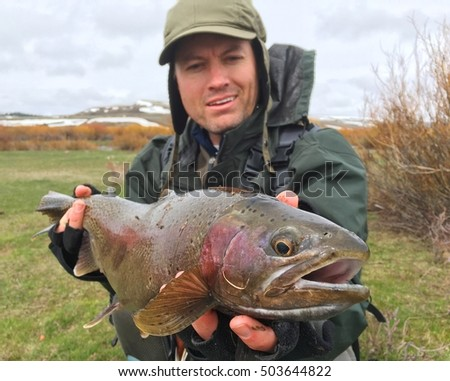Fisherman holding trophy fish - Rainbow Trout (macro focus on head of fish)