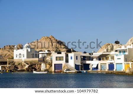 fisherman houses built into rock cliffs on Mediterranean Sea Firopotamos  Klima Milos Cyclades Greek Island Greece - stock photo