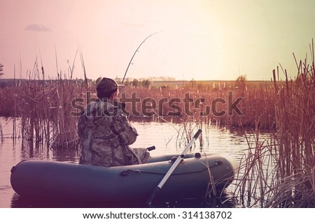 fisherman in a boat, vintage toning - stock photo