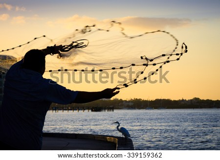 Fisherman in Florida throws net into bay - stock photo