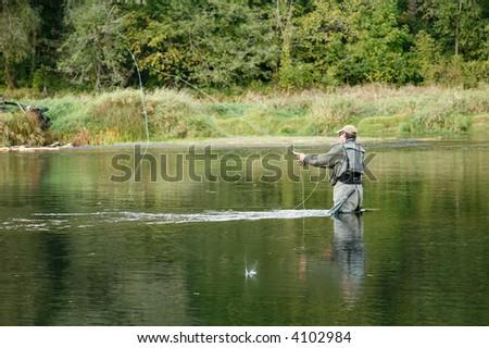 fisherman in river - stock photo