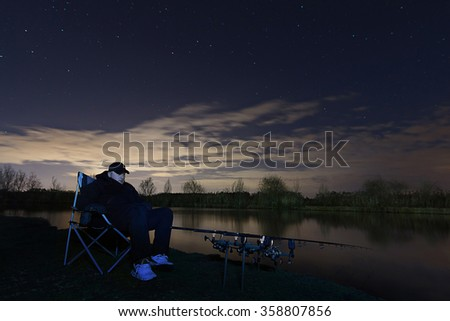 Fisherman in Starry Night, Sitting in chair looking on rods, patience - stock photo