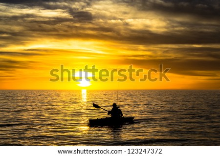 Fisherman in the kayak on the ocean in front of dramatic sunset - stock photo