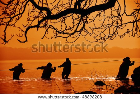 Fisherman in the water - stock photo