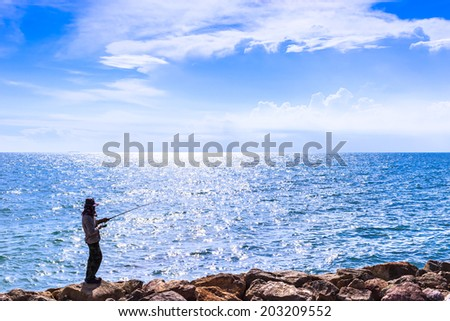 fisherman is  angling in  the sea under cloudy blue sky  - stock photo