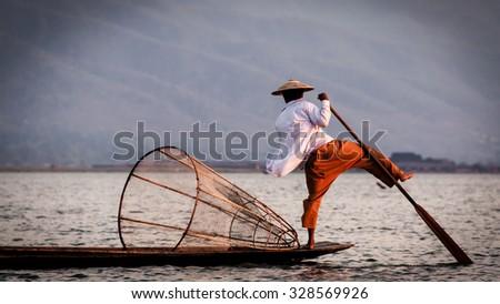 Fisherman leg rowing on the Inle Lake in Myanmar Burma - stock photo