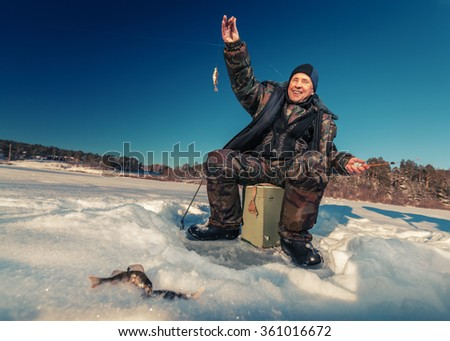 Fisherman on a lake at winter sunny day - stock photo