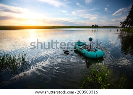 Fisherman on the boat watching sunset over the pond - stock photo