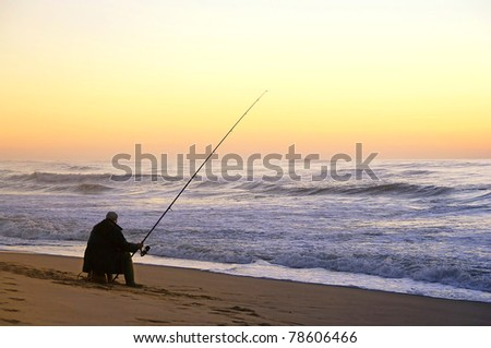fisherman seated in the beach - stock photo