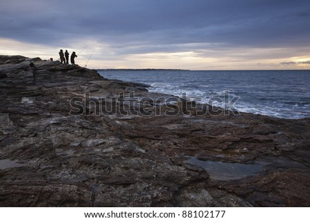 Fisherman silhouette at sunrise getting an early start along this rocky coastline. - stock photo