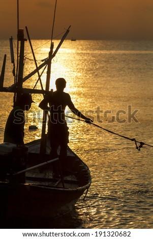 Fisherman silhouette in sea at sunrise - stock photo