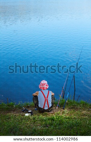 Fisherman sitting on a coast of pond and waiting a fish - stock photo