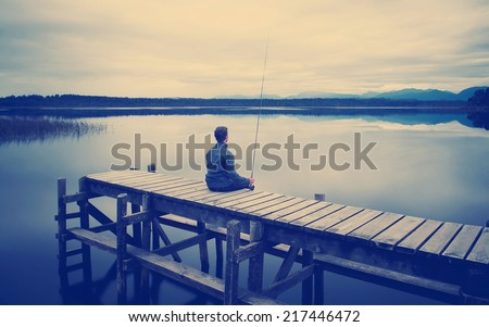 Fisherman sitting on a jetty on a moody winters day with Instagram style filter - stock photo