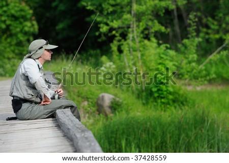 Fisherman sitting on the bridge - stock photo