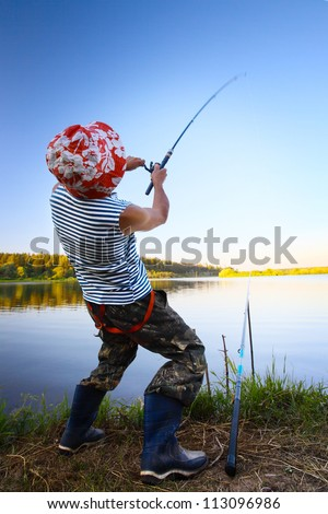 Fisherman standing on a coast of pond and pulling a fish - stock photo