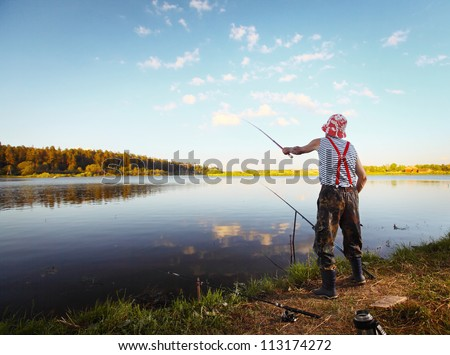 Fisherman standing on a coast of pond with fishing rod and throwing a bait