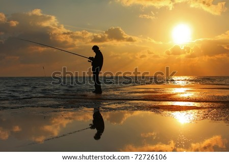 Fisherman standing on a pier at dawn sky background - stock photo