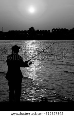 Fisherman standing on edge of dock with fishing rod near river and beach town in rays of sunset black and white