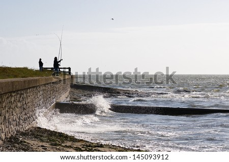 Fisherman throwing line on atlantic French coast - stock photo