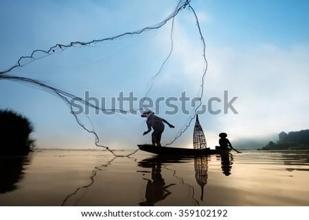 Fisherman throwing net at sunrise, Mae Klong River, Thailand - stock photo