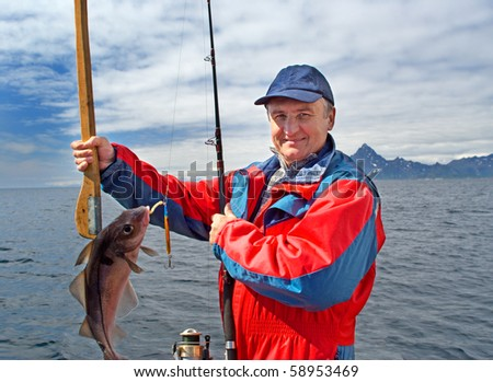 Fisherman with a fish on the Lofoten island - stock photo