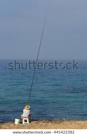 Fisherman with a fishing rod and the blue Mediterranean Sea