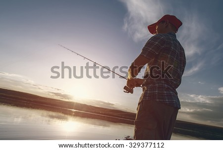 Fisherman with a fishing rod in the pond with a sunset on the background - stock photo