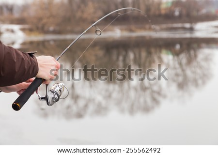 Fisherman with a fishing rod on the river bank - stock photo