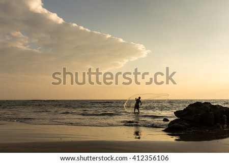 Fisherman with a net on sunset. Arabian sea. India - stock photo