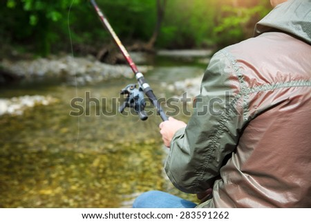 Fisherman with fly-fishing on mountain river. Spring time - stock photo