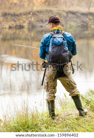 Fisherman with spinning - autumn fishing season. - stock photo