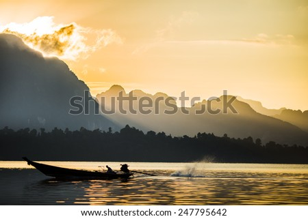 Fisherman working in morning. Background is mountain and beautiful light of sunbeam. - stock photo