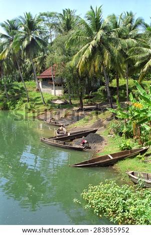 Fishermen and boats at a river near Pangandaran, Java, Indonesia - stock photo