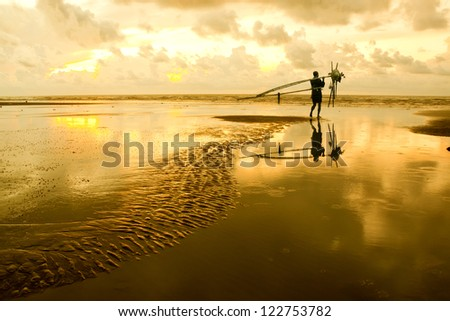 Fishermen at dawn sky background with sun rays and reflected in - stock photo