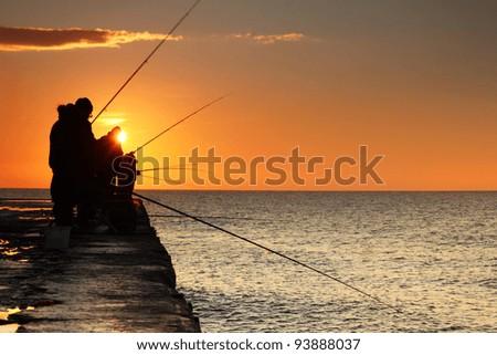 Fishermen at sunrise on the sea - stock photo