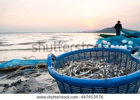 Fishermen catch fish in a basket from the river. - stock photo
