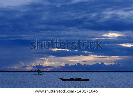 Fishermen Dhow Boat coming back home at sunset from a long day in the sea. Taken at Nungwi village, Zanzibar Island, Tanzania - stock photo