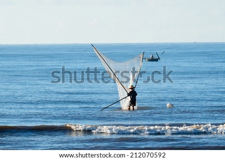 Fishermen fishing in the sea at early morning in Namdinh, Vietnam.They wake up at 4am and go out to sea to wait until the sun rises. They use a small net to scoop the seafood near the beach. - stock photo