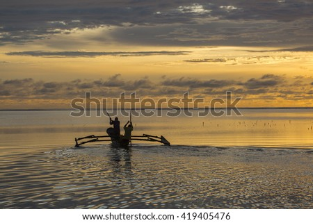 Fishermen going on ocean on traditional fishing boat in Zanzibar with storm clouds at sunrise