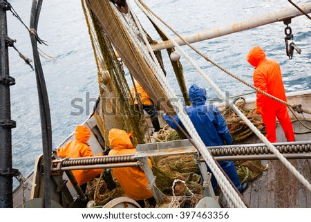Fishermen in waterproof clothing on the deck of the fishing vessel. Morning time.