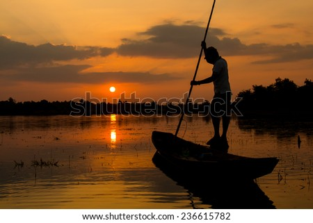 fishermen on a boat at sunrise - stock photo