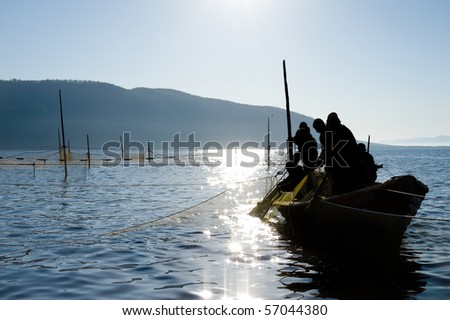 fishermen on a boat haul a seine - stock photo