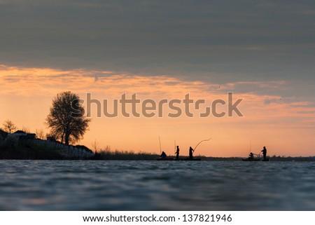 Fishermen on sunrise on the lake - stock photo