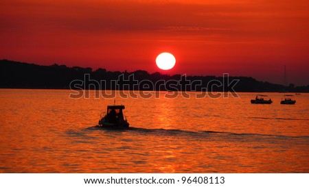 Fishermen silhouette on sea at red sunset near Brioni national park