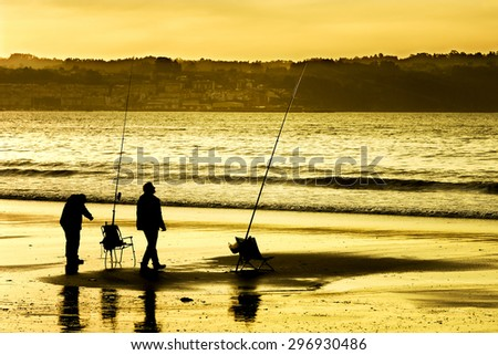 fishermen silhouette with blue sky and red on the beach at dusk  - stock photo